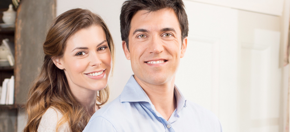 A man and woman smiling and looking at the camera