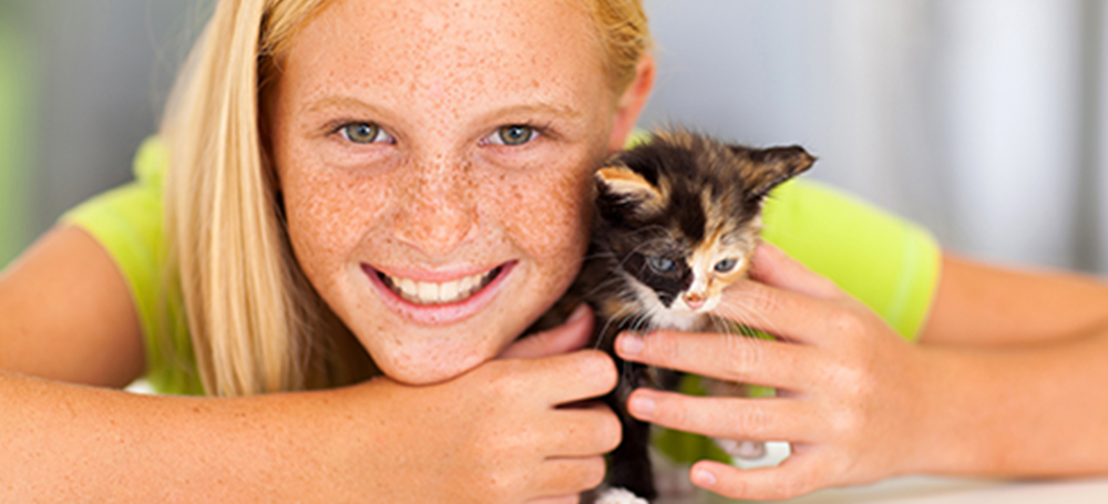 A young girl with blonde hair and freckles, smiling and holding a multi-colored kitten